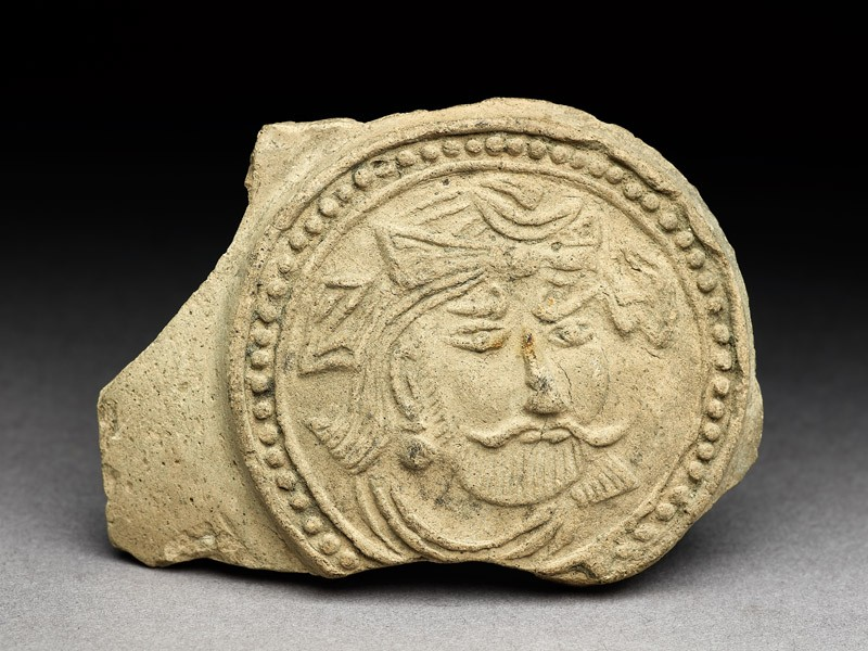 Medallion from a pot depicting a bearded figure, possibly a bodhisattva (EA1984.26, front           )
