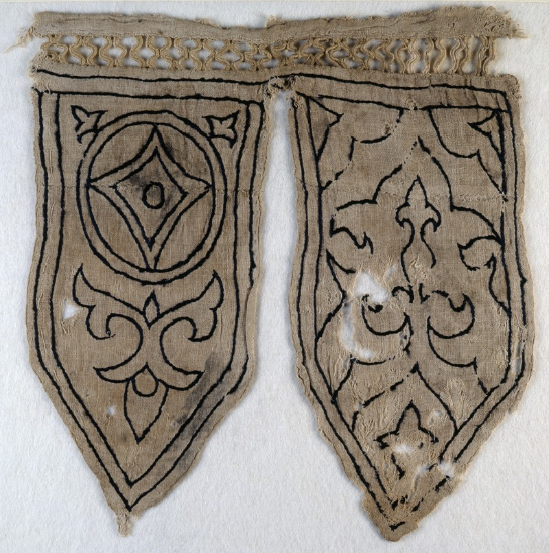 Tabs from a banner with fleur-de-lys, blazon, and trefoils