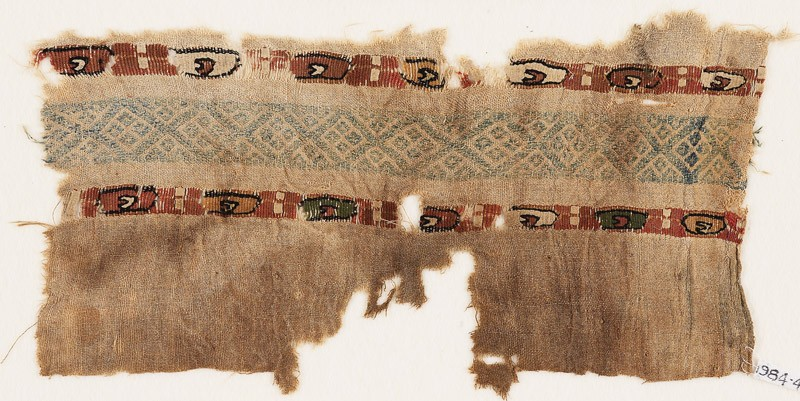 Textile fragment with two bands of ovals containing small crescents (front            )