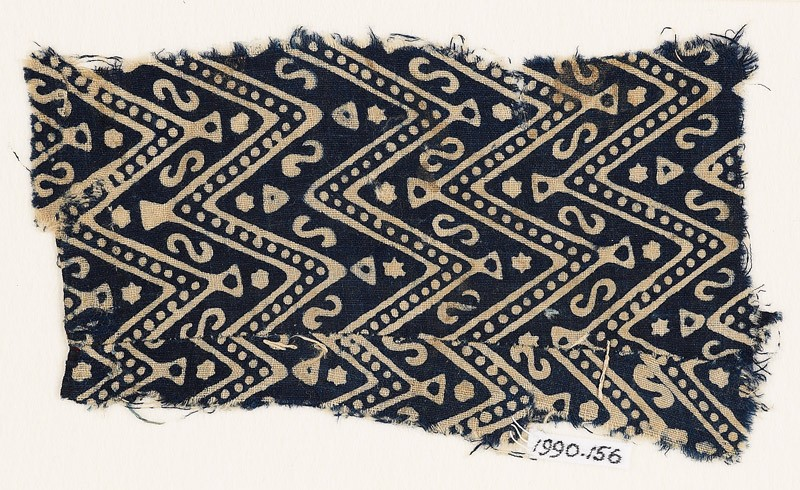 Textile fragment with large chevrons, dots, S-shapes, and stars