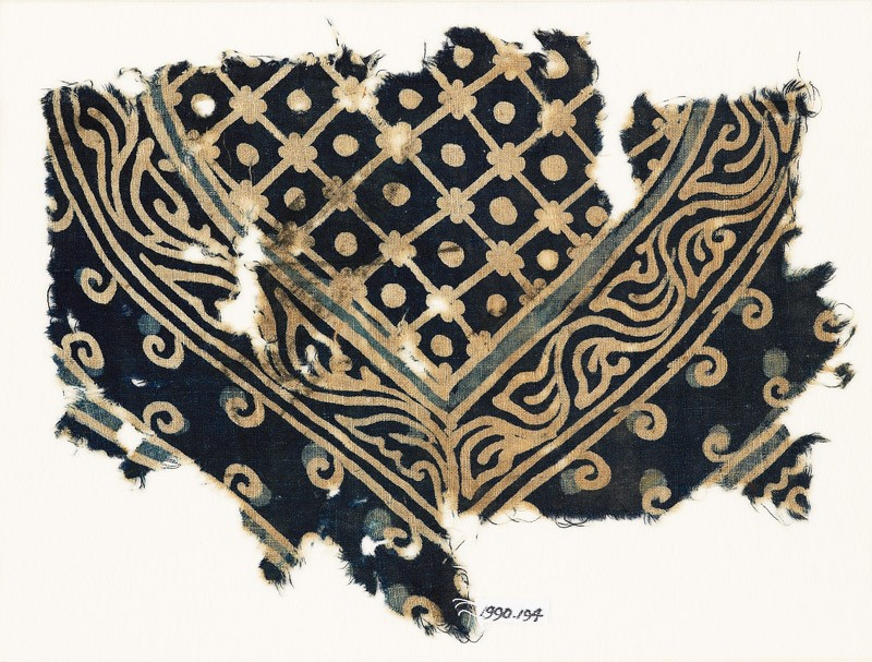 Textile fragment with part of a large medallion with a grid, dots, and a vine (front            )