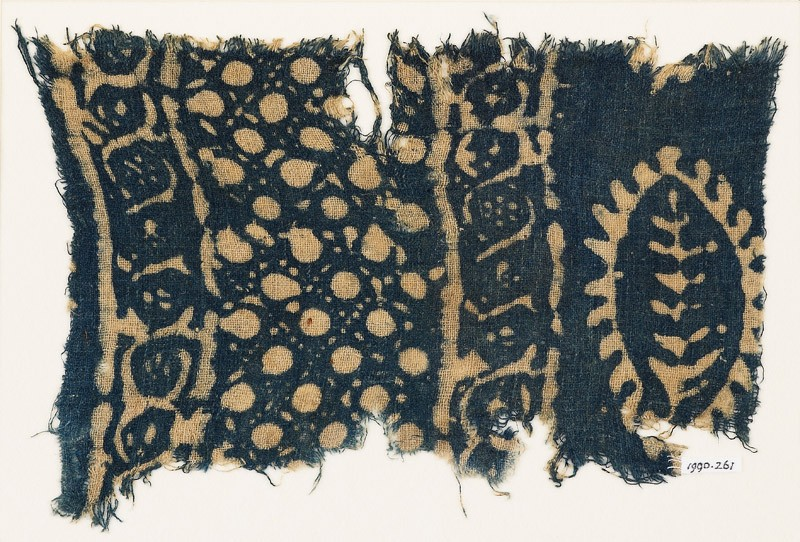 Textile fragment with vines, dots in a grid, and probably a leaf