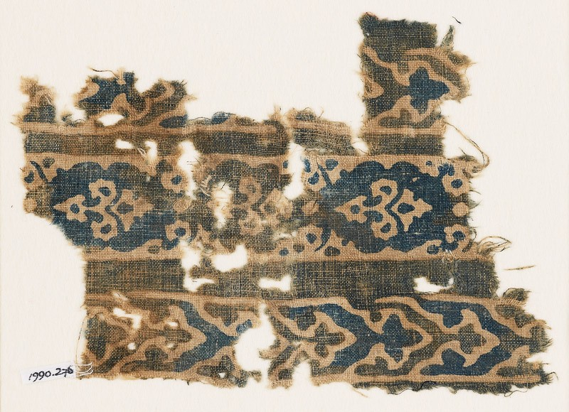 Textile fragment with bands of flowers and elaborate chevrons (front            )
