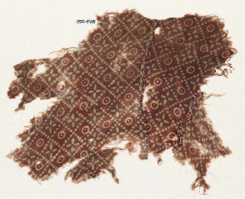 Textile fragment with grid of dots, circles, and rosettes, probably from a garment