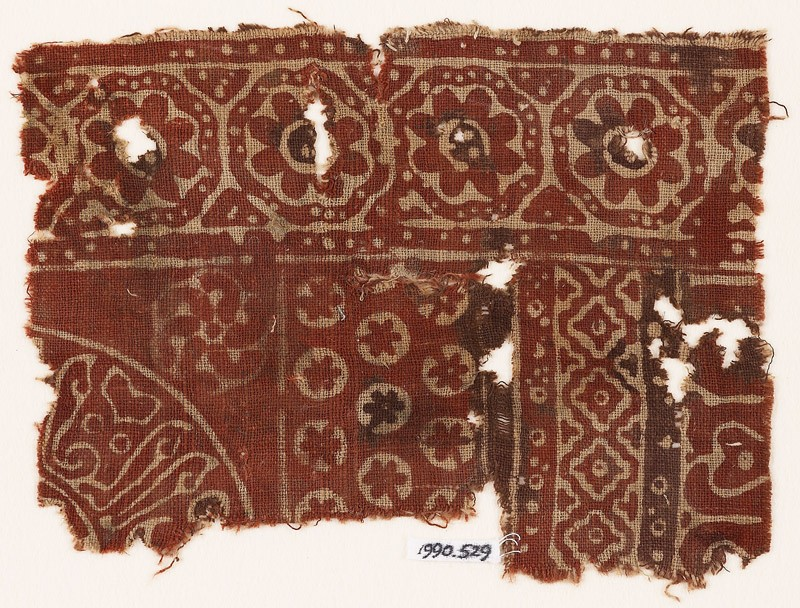 Textile fragment with rosettes in dotted frames, linked diamond-shapes, and Arabic inscription (front            )