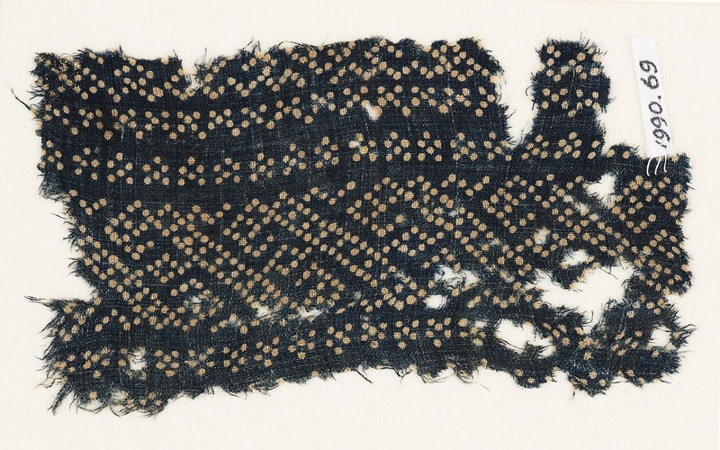 Textile fragment with dots arranged in a geometric pattern