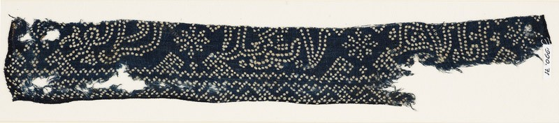 Textile fragment with geometric patterns, stars, and possibly script made of dots