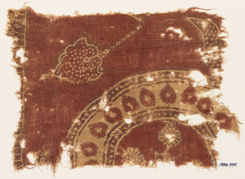 Textile fragment with part of a large circle and leaves