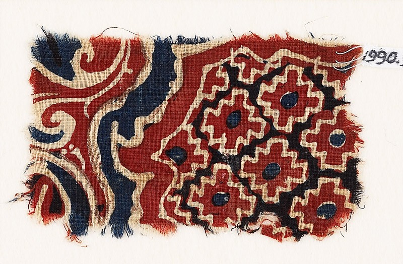 Textile fragment with stepped diamond-shapes and swirling plants (front            )