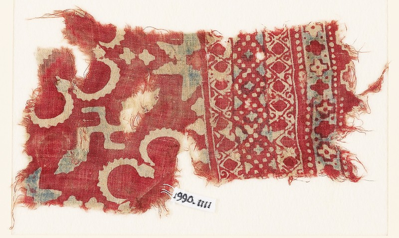 Textile fragment with stars, swastika, and possibly rosettes (EA1990.1111, front             )
