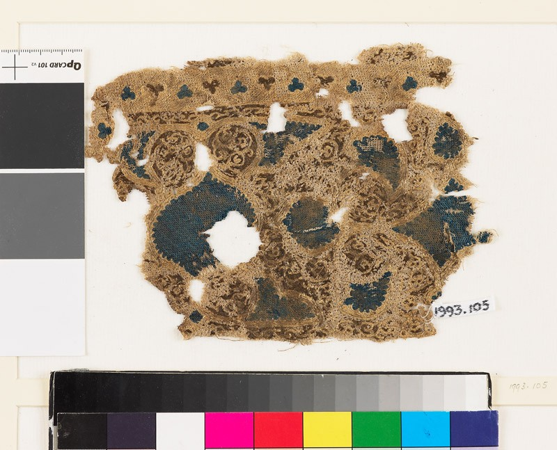 Textile fragment with swirling vegetal pattern and trefoil shapes (front            )