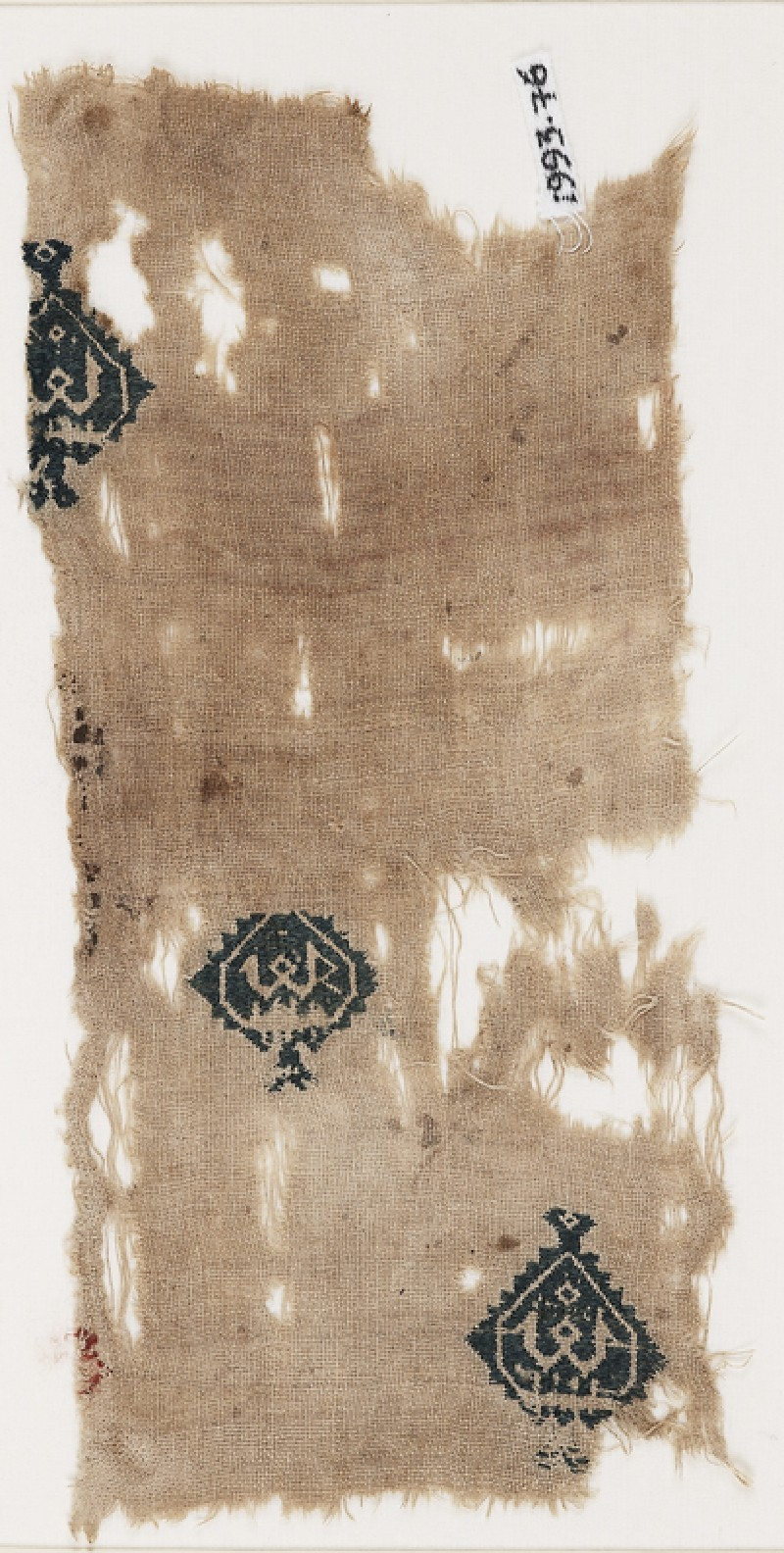 Textile fragment with diamond-shaped medallions containing a pseudo-Kufic word (front           )