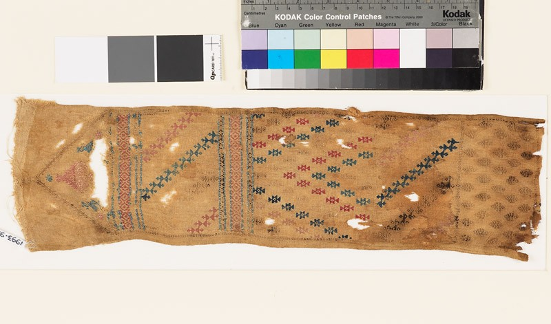 Textile fragment with geometric shapes and a diamond-shaped medallion