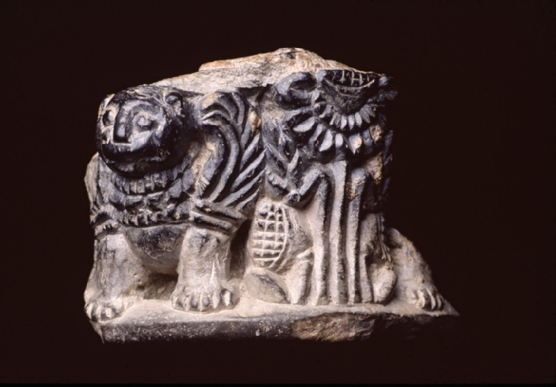 Fragmentary object, possibly the pedestal or foot of a pot, carved with figures of winged lions and lotus (EA1994.105)