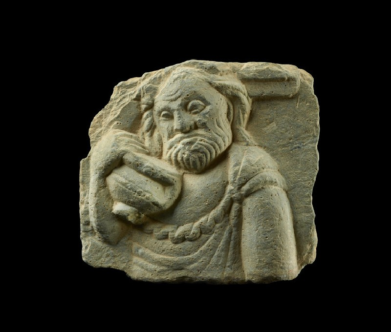 Relief fragment depicting an old man holding a large vessel