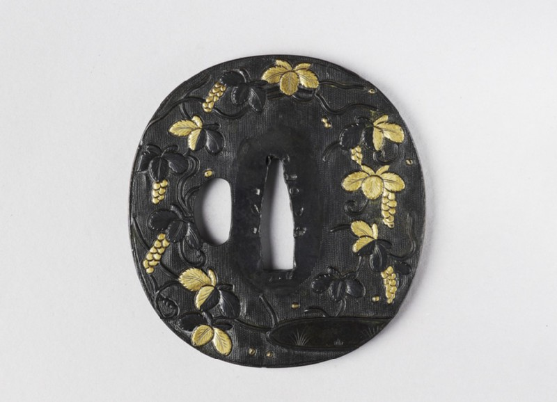 Round tsuba with design of wisteria plants and pond (front            )