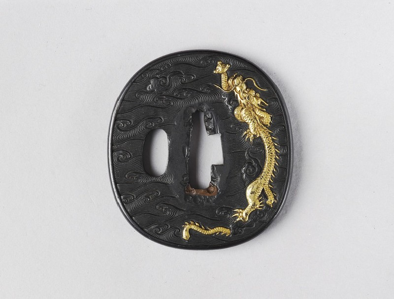 Round tsuba with design of dragon and waves