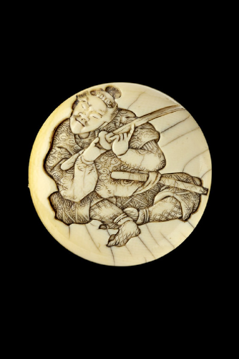 Manjū netsuke depicting a samurai testing the sharpness of his sword blade (EA2001.132)