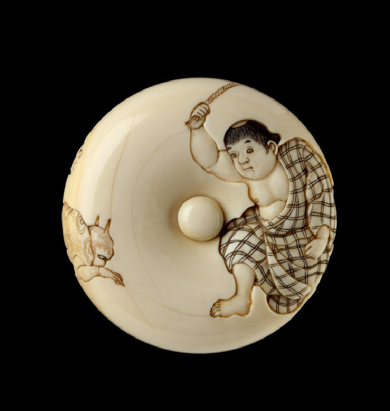 Manjū netsuke depicting a boy chasing away two oni, or demons