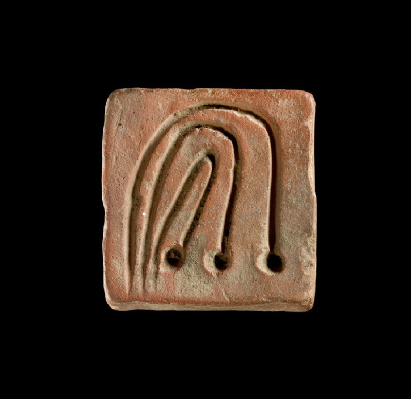 Squarish object incised with three curved lines and dots, probably a game counter, weight or sealing (EAX.147.a)