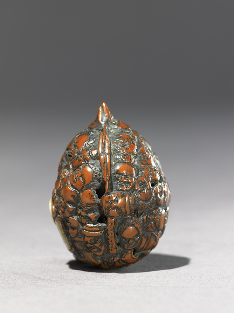 Netsuke formed from a walnut shell, carved all over with masks (EAX.1345, side          )