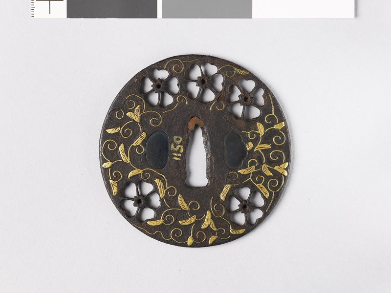 Round tsuba with cherry blossoms and karakusa, or scrolling plant pattern (front           )