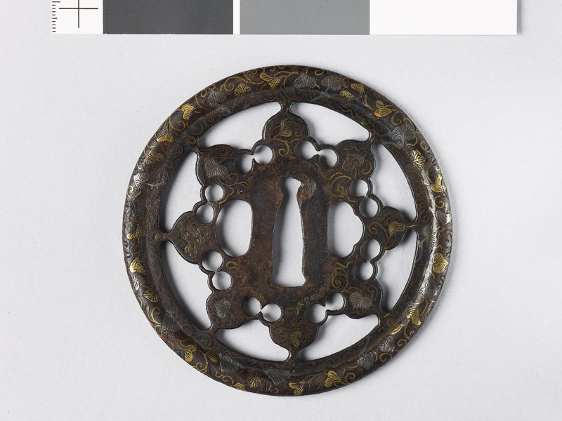 Round tsuba with karakusa, or scrolling plant pattern, interspersed with aoi, or wild ginger (EAX.10147, front           )
