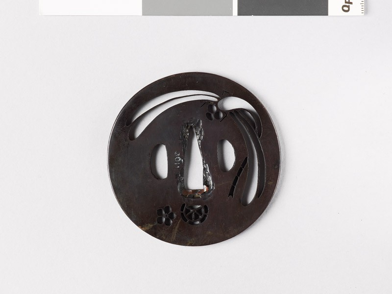 Round tsuba with mon formed from clematis flower and chariot wheel (front           )