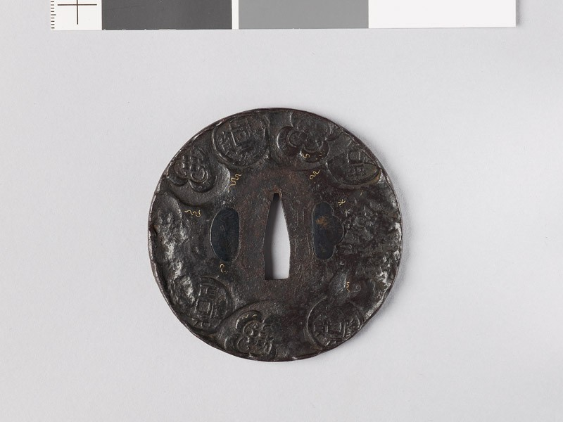 Round tsuba depicting old Chinese coins among mokkō shapes and scrolls