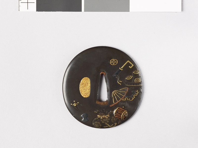 Lenticular tsuba with takaramono, or precious things (front           )