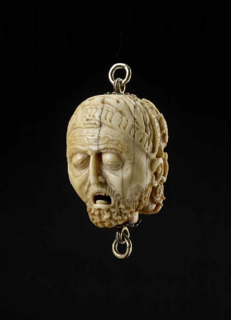 Ivory Memento Mori pendant with a dead man's face and a decaying skull with worms and other creatures (WA2013.1.30)