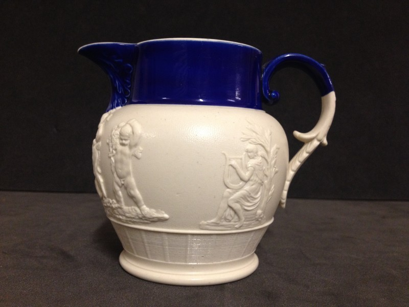 Jug with 'C' scroll and spur handle, neck and handle coloured blue. Sides decorated with figures of Orpheus, Calliope and Bacchanalian boys