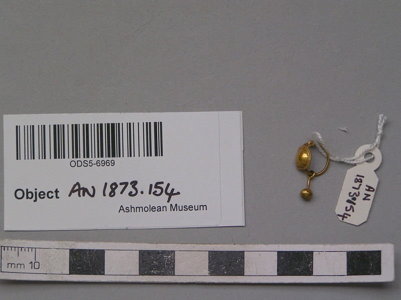 Gold earring with round cup-shaped upper part and solid ball attached to suspended stem below