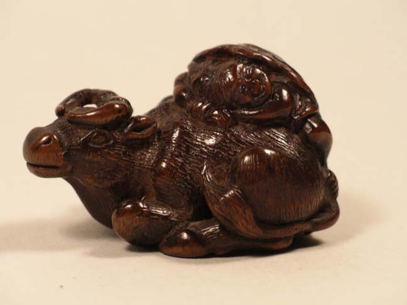 Netsuke in the form of an ox sitting down with a herdboy asleep on its back (EA1956.3269, record shot)