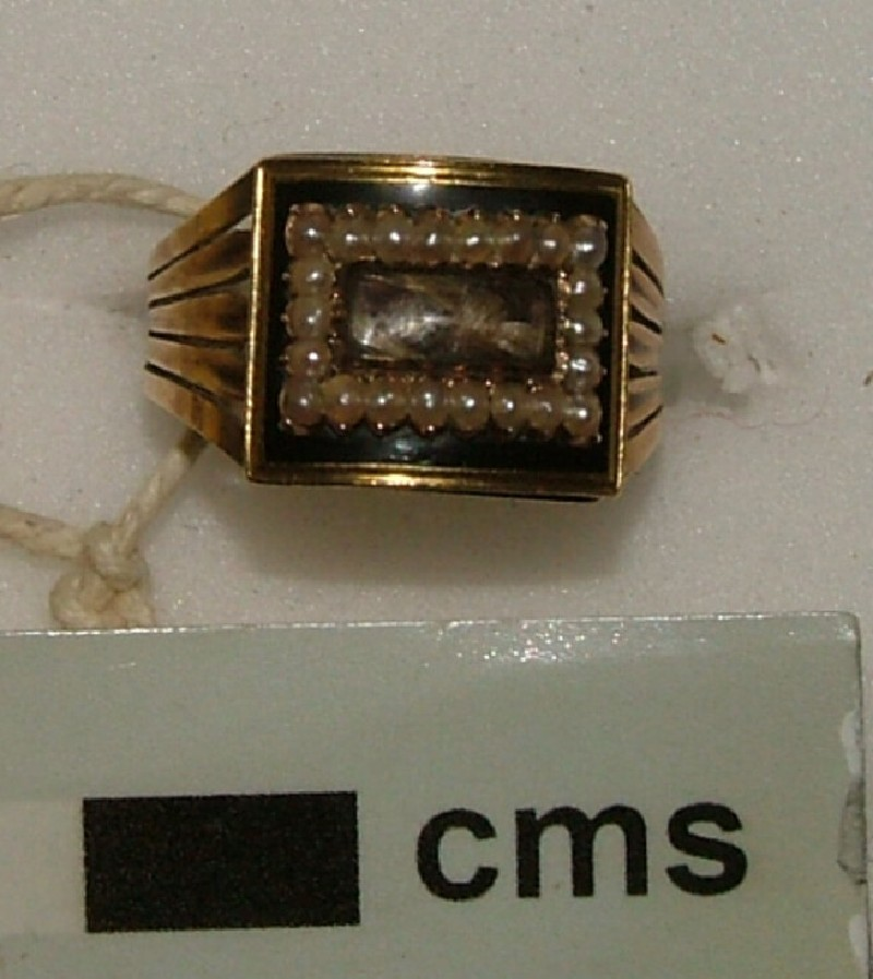 Gold mourning ring, the rectangular bezel with hair in centre framed by a seed pearl border and outer border of black enamel, expanding hoop of three section