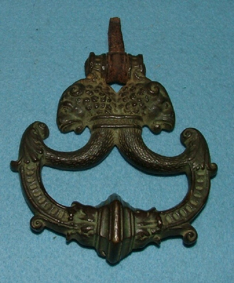 Small door knocker or handle ornamented with rams' heads strapped together `dos-à-dos'