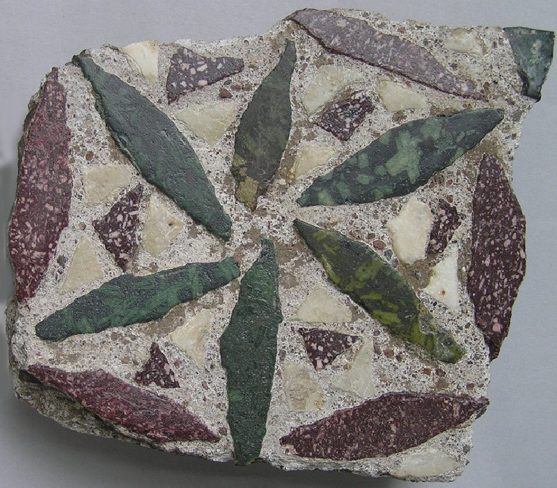 Paving stone decorated with a flower and leaves in purple and green porphyry, recycled from Roman use