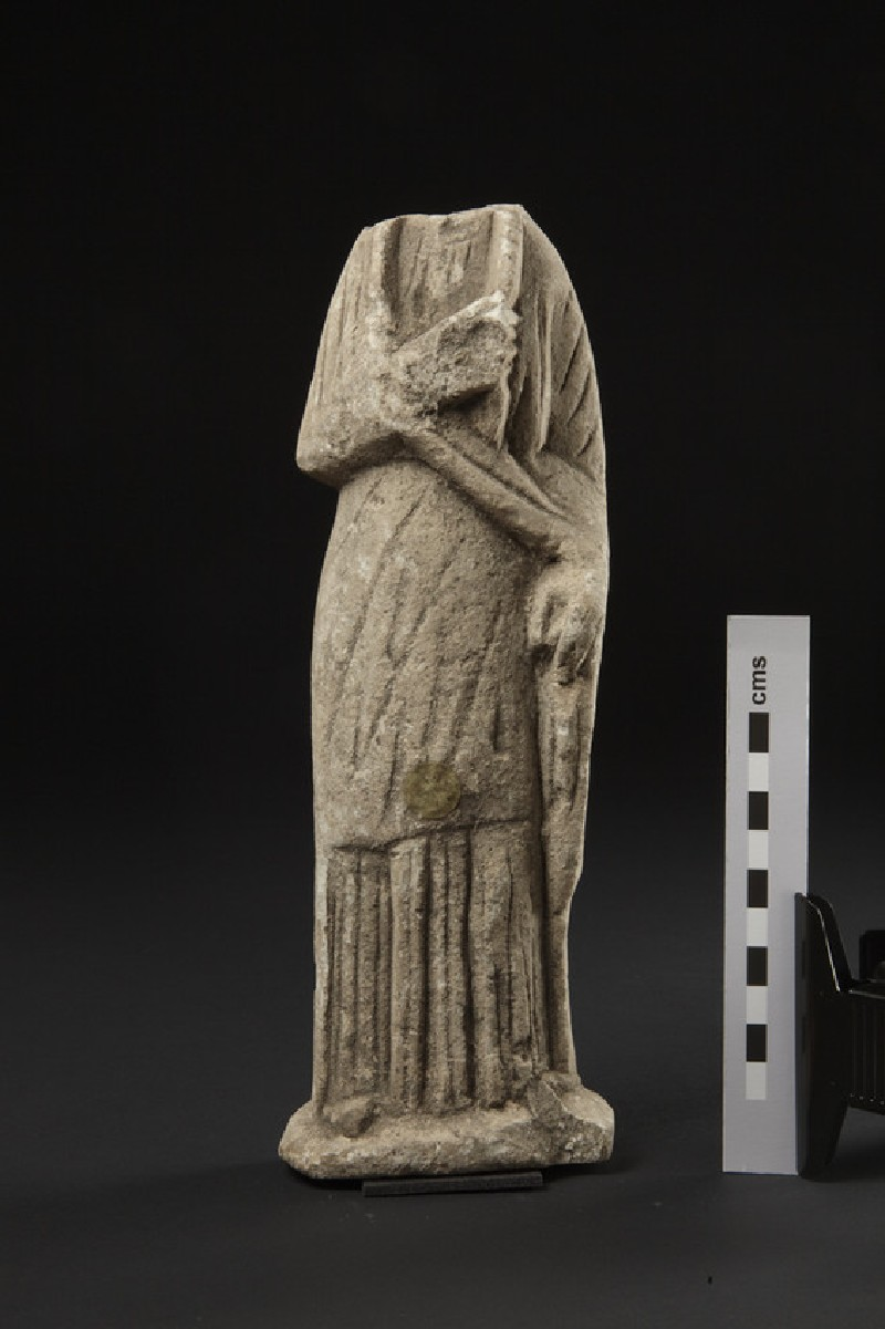 Limestone headless female votary with himation pulled over the missing head, votive-statuette