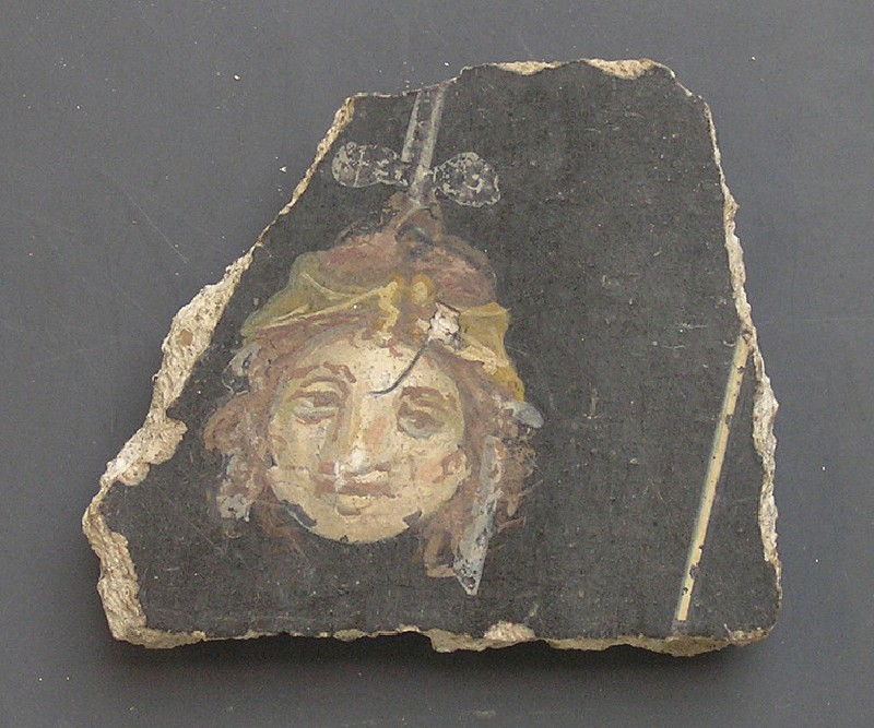 Fragment of painted wall plaster depicting suspended mask on a black ground