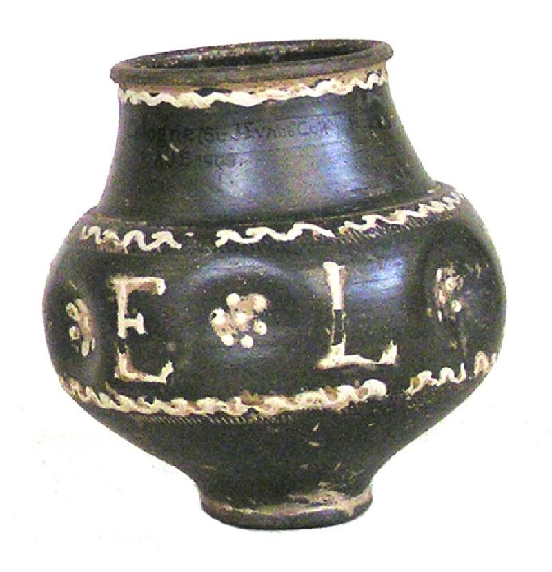 Black Rhenish ware indented beaker with white barbotine decoration inscribed FELIX
