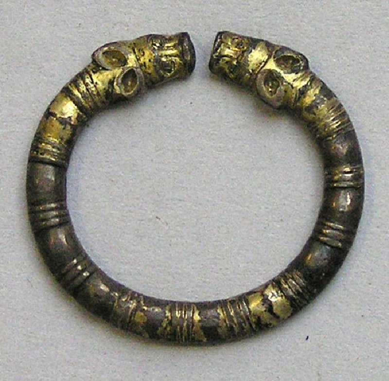 Penannular silver ring terminating in animal's heads