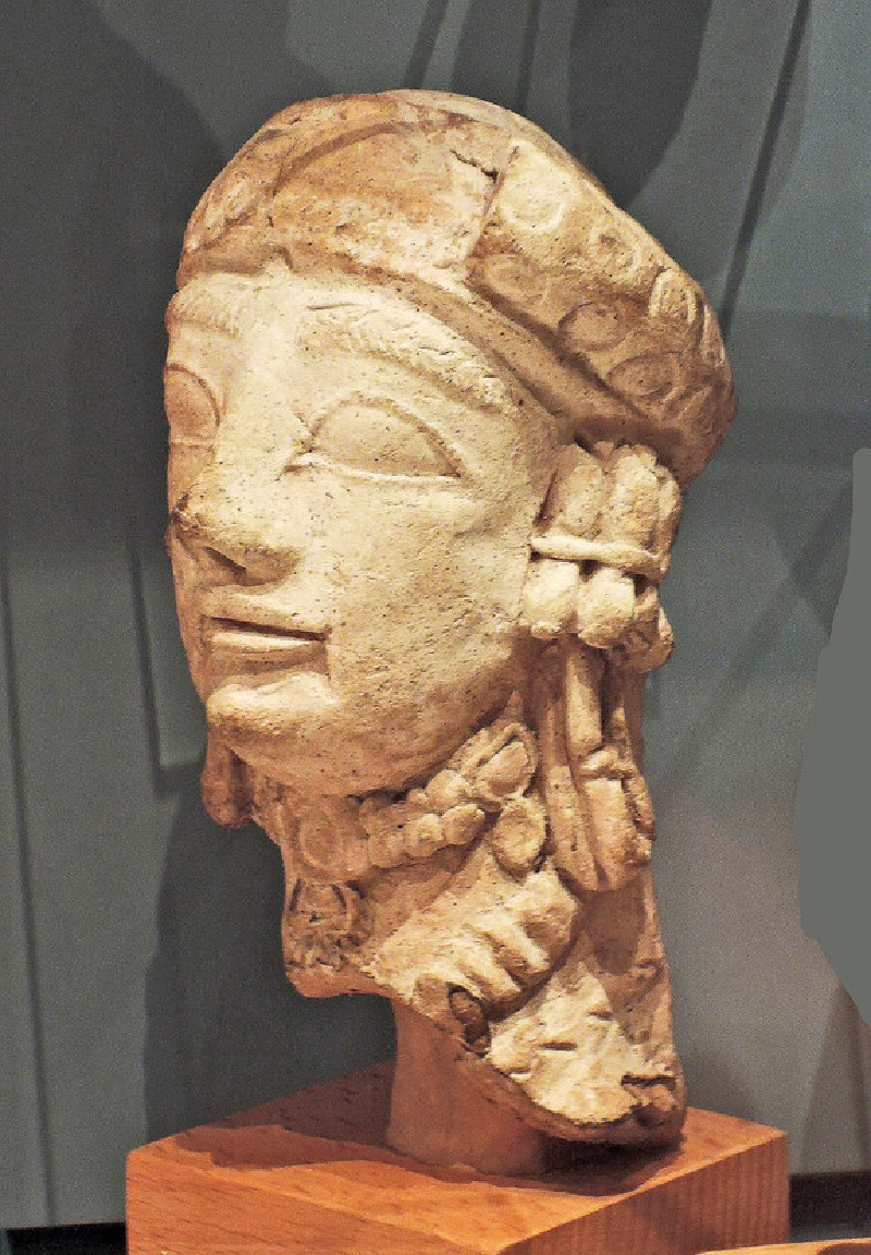 Terracotta head of female votary figurine with turban and rich jewellery (AN.1926.551)