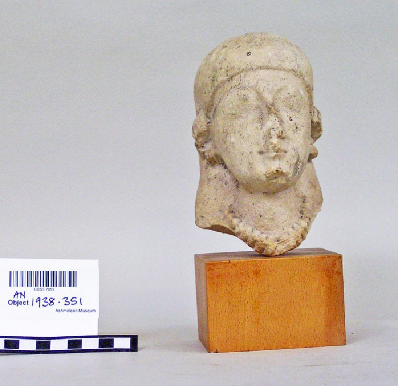 Head of female votary with veil and Cypriot earcaps, votary sculpture fragment (AN.1938.351)
