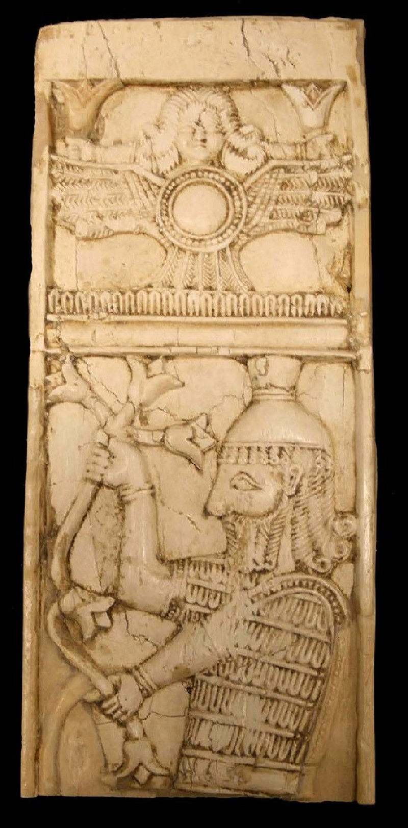 Ivory plaque depicting panel containing the solar disc with wings and tail-feathers, mounted by a female head (AN1959.206, AN.1959.206, record shot)