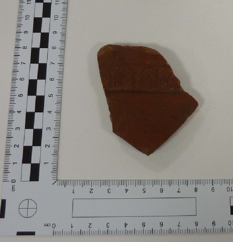 Sherd of Samian bowl with egg and dart border, beaded line, and winding scroll