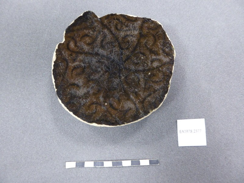 Base fragment of a vessel with scrolls