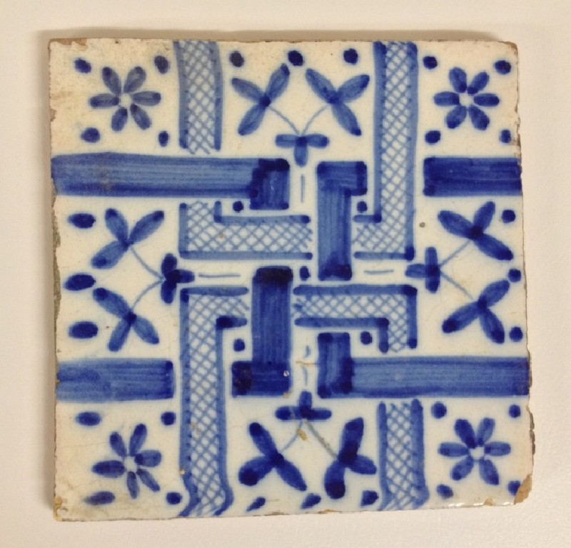 Tile with interlocking geometric pattern with leaves and flower heads